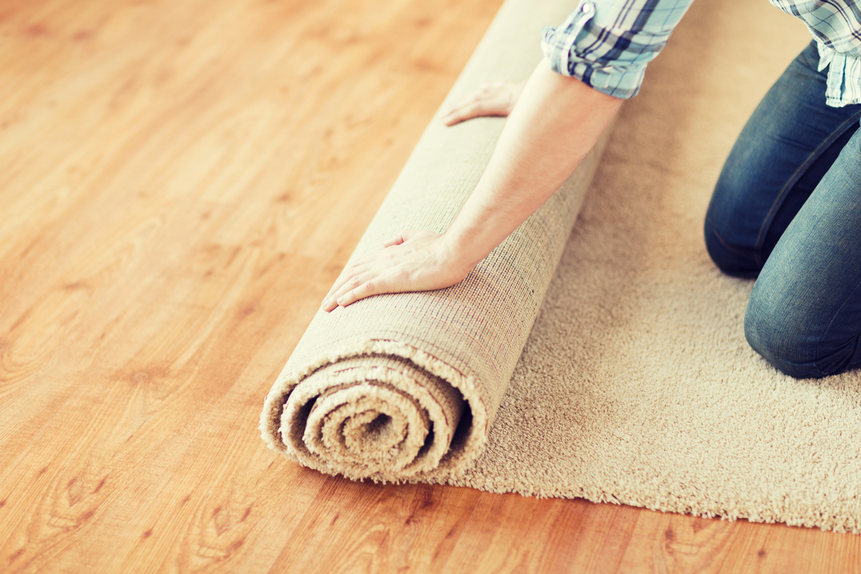Carpet being rolled out onto hardwood flooring