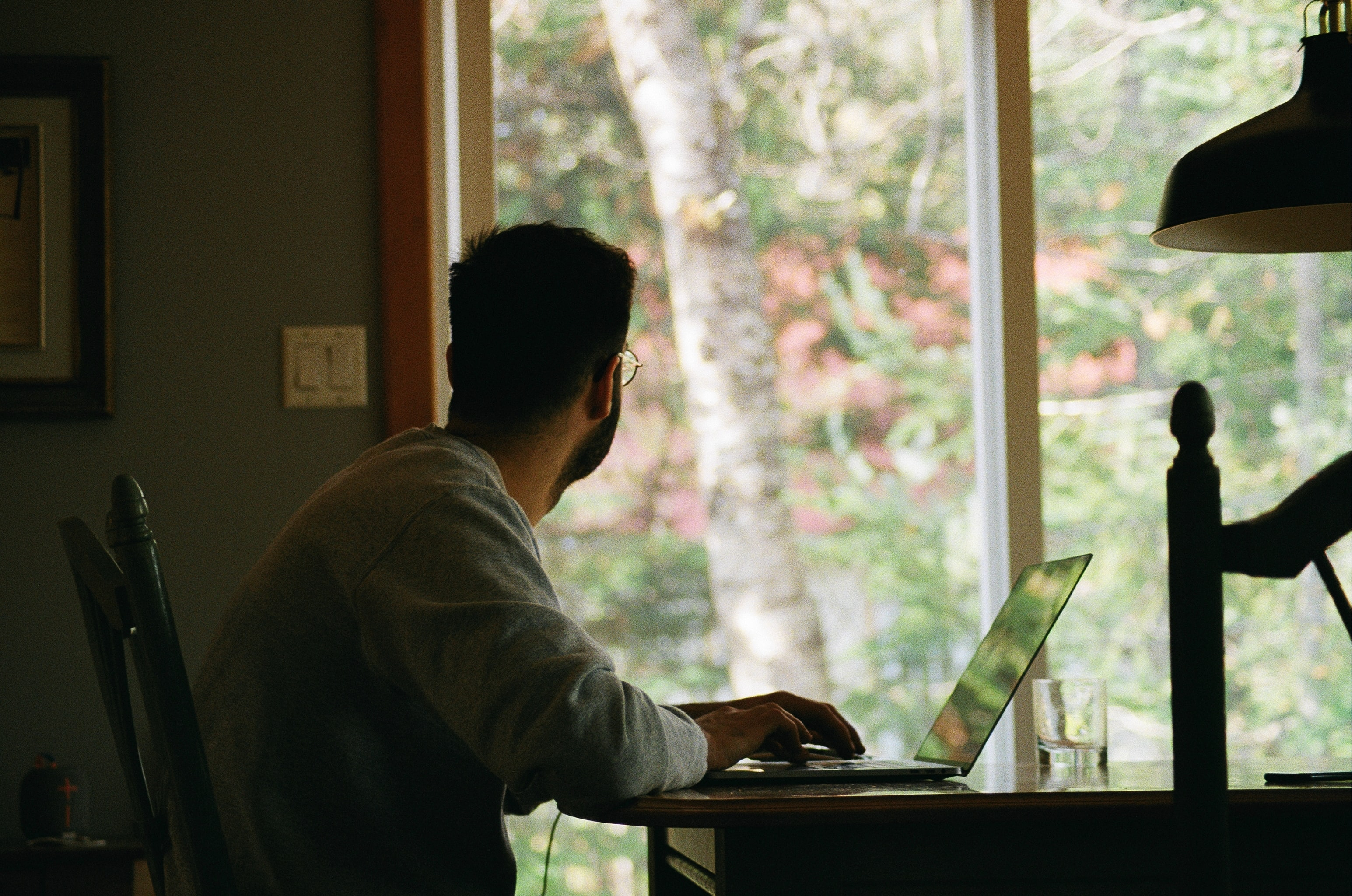A person looks out the window from their home office.