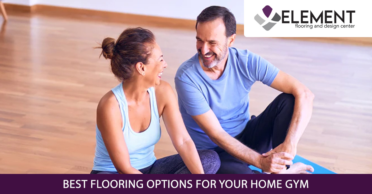 A man and woman sit together on hardwood flooring in their home gym.