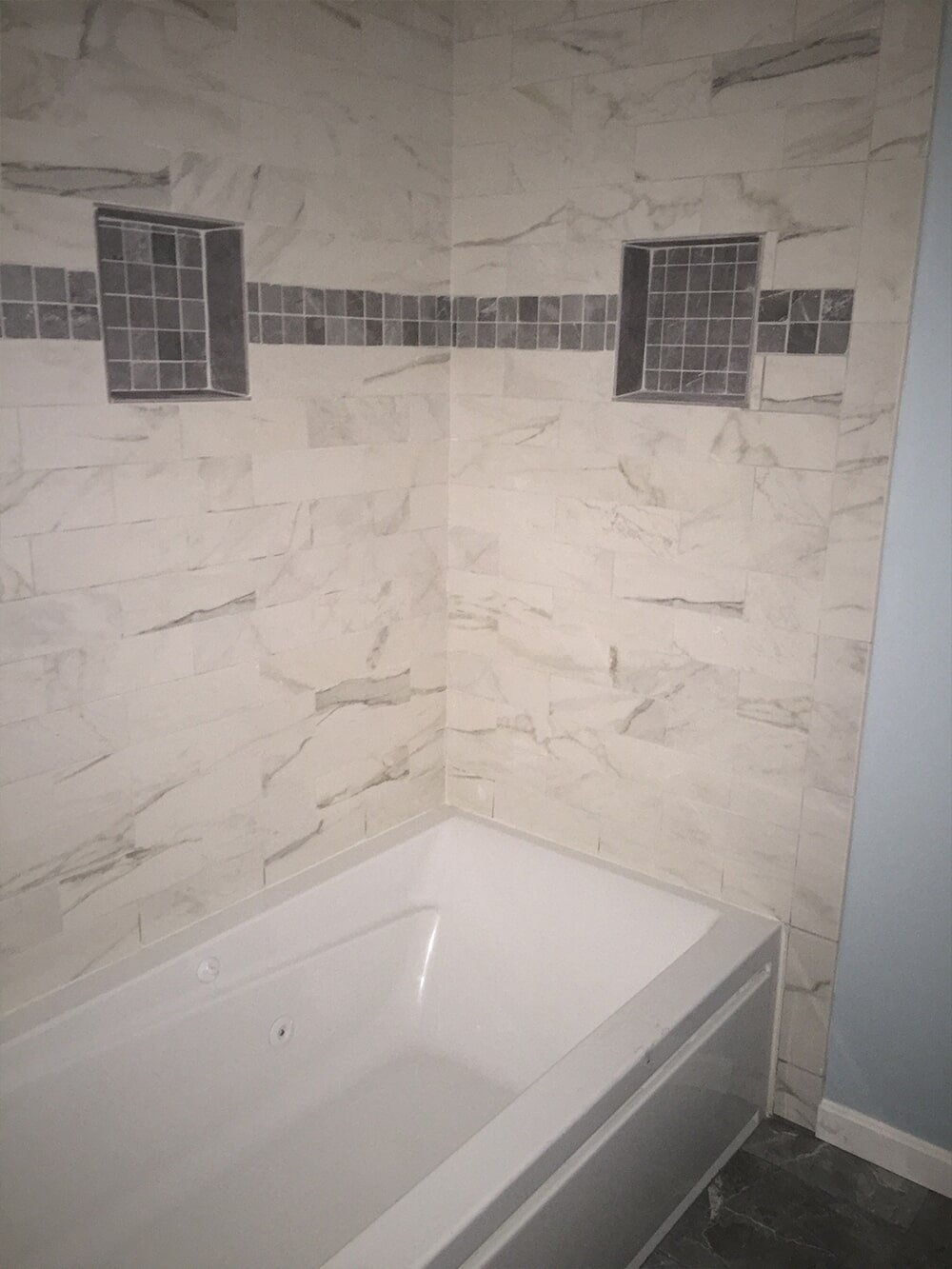 Shower installation with marble tile and accents from  Summerlin Floors
