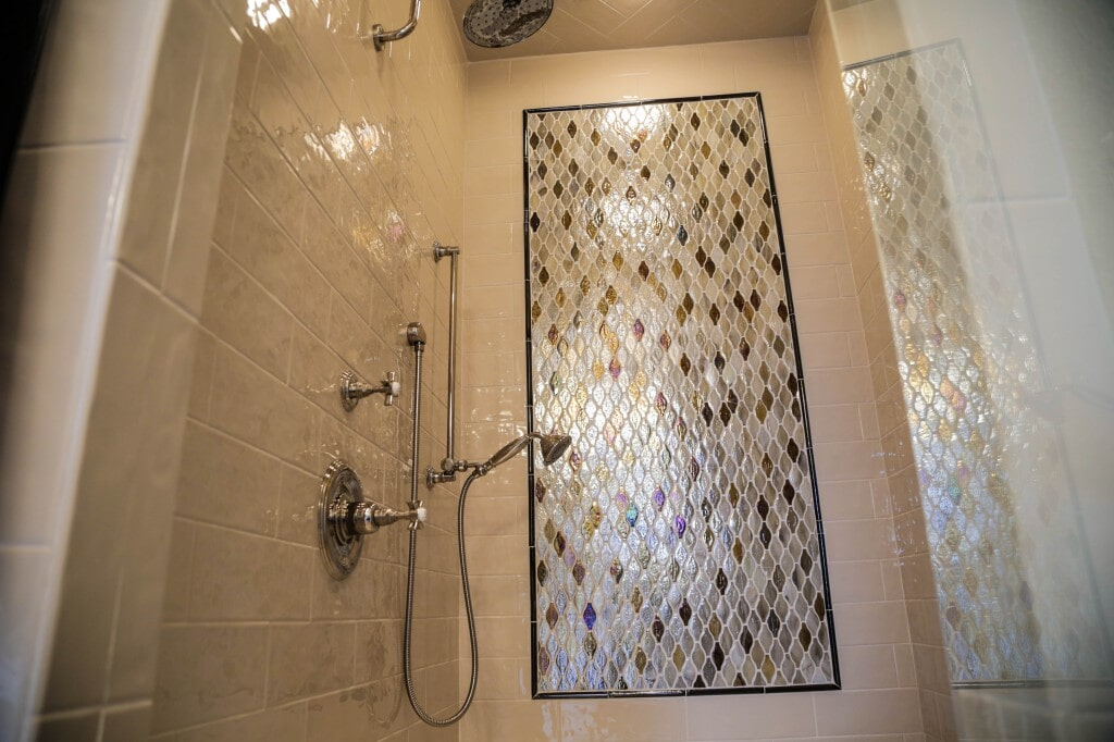 Remodeled shower with unique mosaic tile feature by Yates Flooring Center