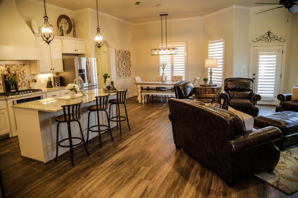 Open concept kitchen and living room with hardwood flooring by Yates Flooring Center