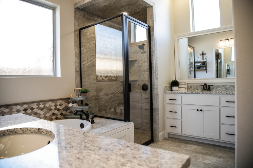 Remodeled bathroom with tile flooring, shower, and bathtub by Yates Flooring Center