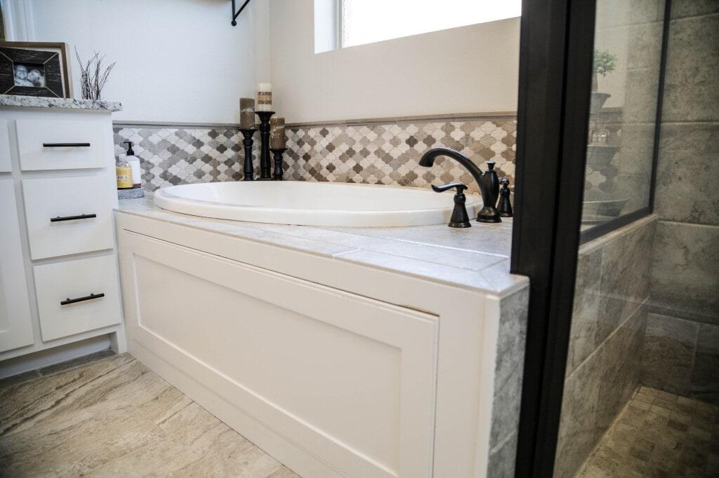 Remodeled bathroom with tile flooring, shower, and backsplash by Yates Flooring Center (2)
