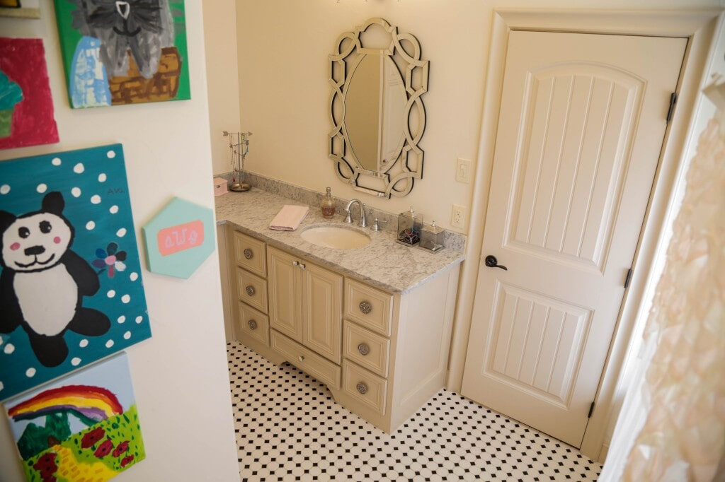 Traditional yet fun bathroom remodel with black and white hexagon tile flooring by Yates Flooring Center
