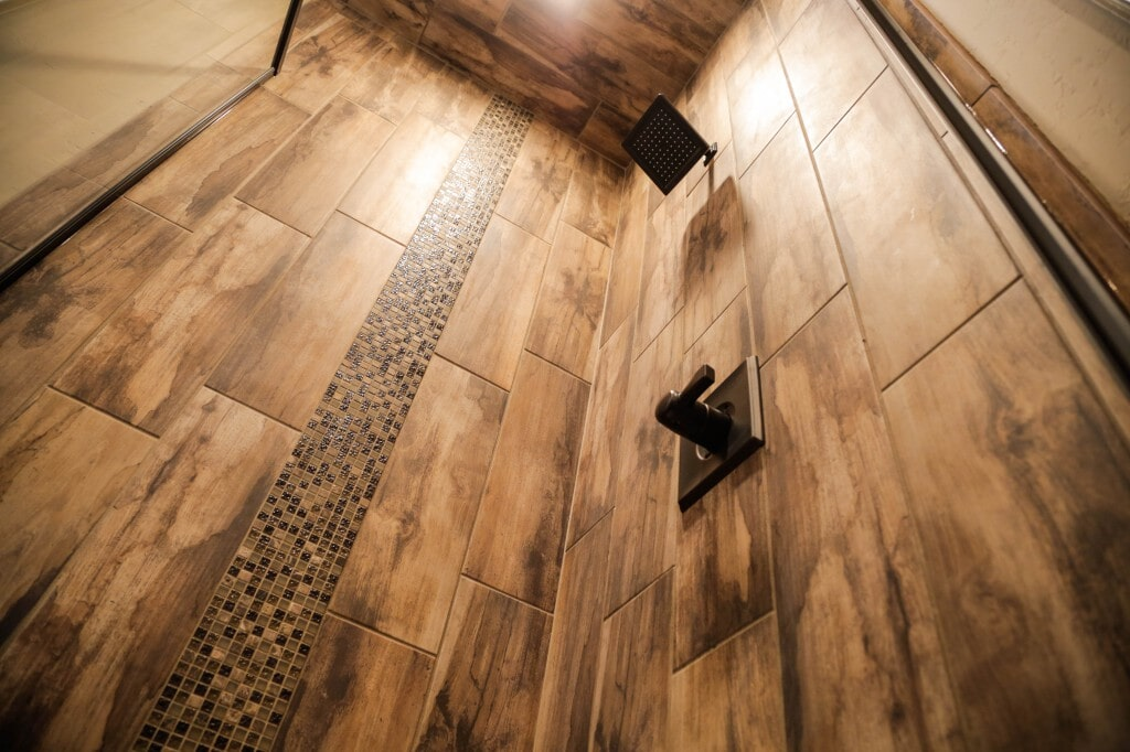 Ultra modern wood look tile shower surround with glass tile mosaic inset and rain shower head by Yates Flooring Center