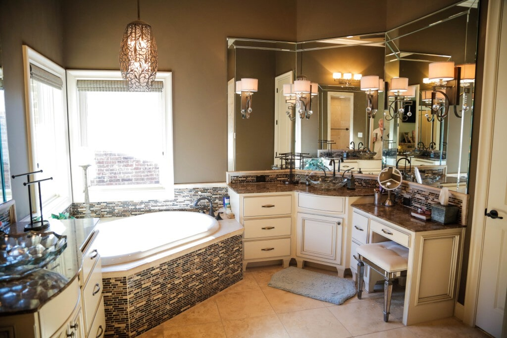 Luxurious bathroom with large format tile flooring and glass tile backsplash throughout by Yates Flooring Center