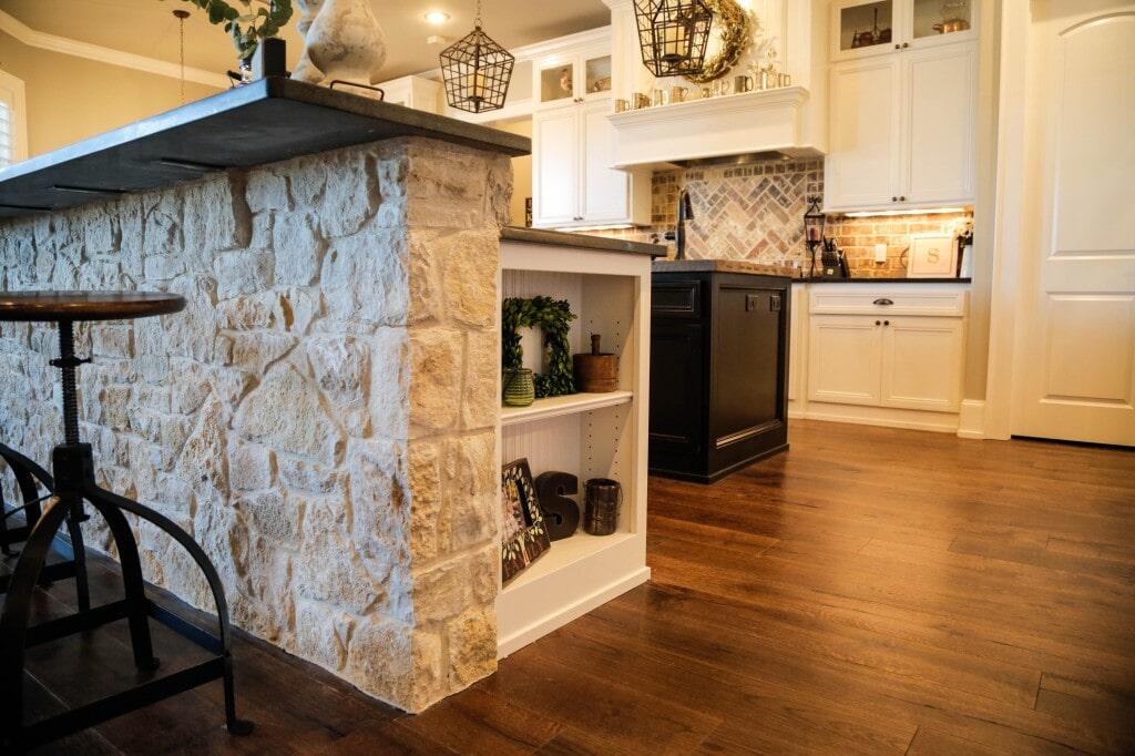 Mixed material kitchen with natural stone bar, tile backsplash and hardwood flooring by Yates Flooring Center