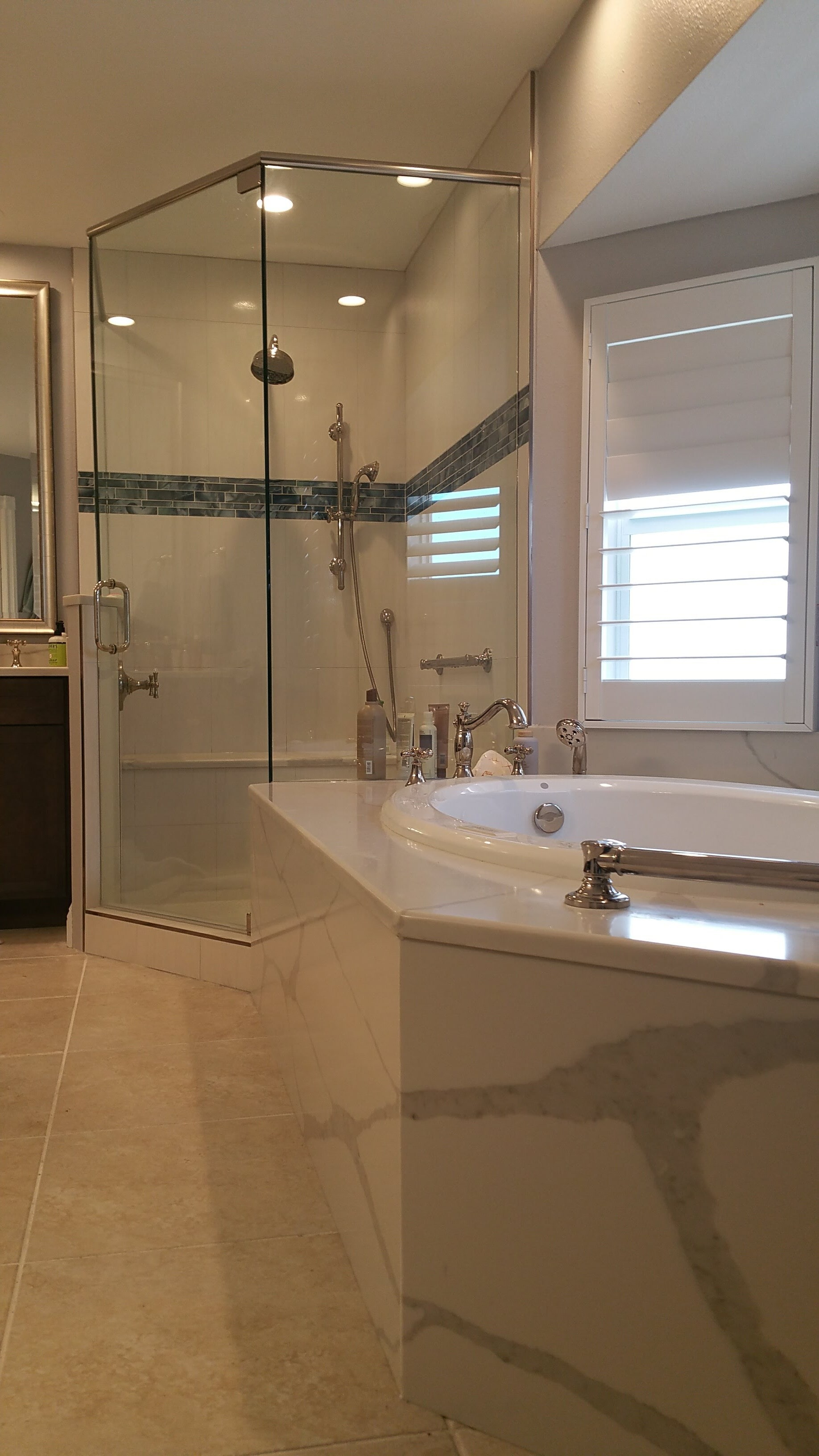 Corner shower with shower bench and quartz tub deck from Relo Interior Services