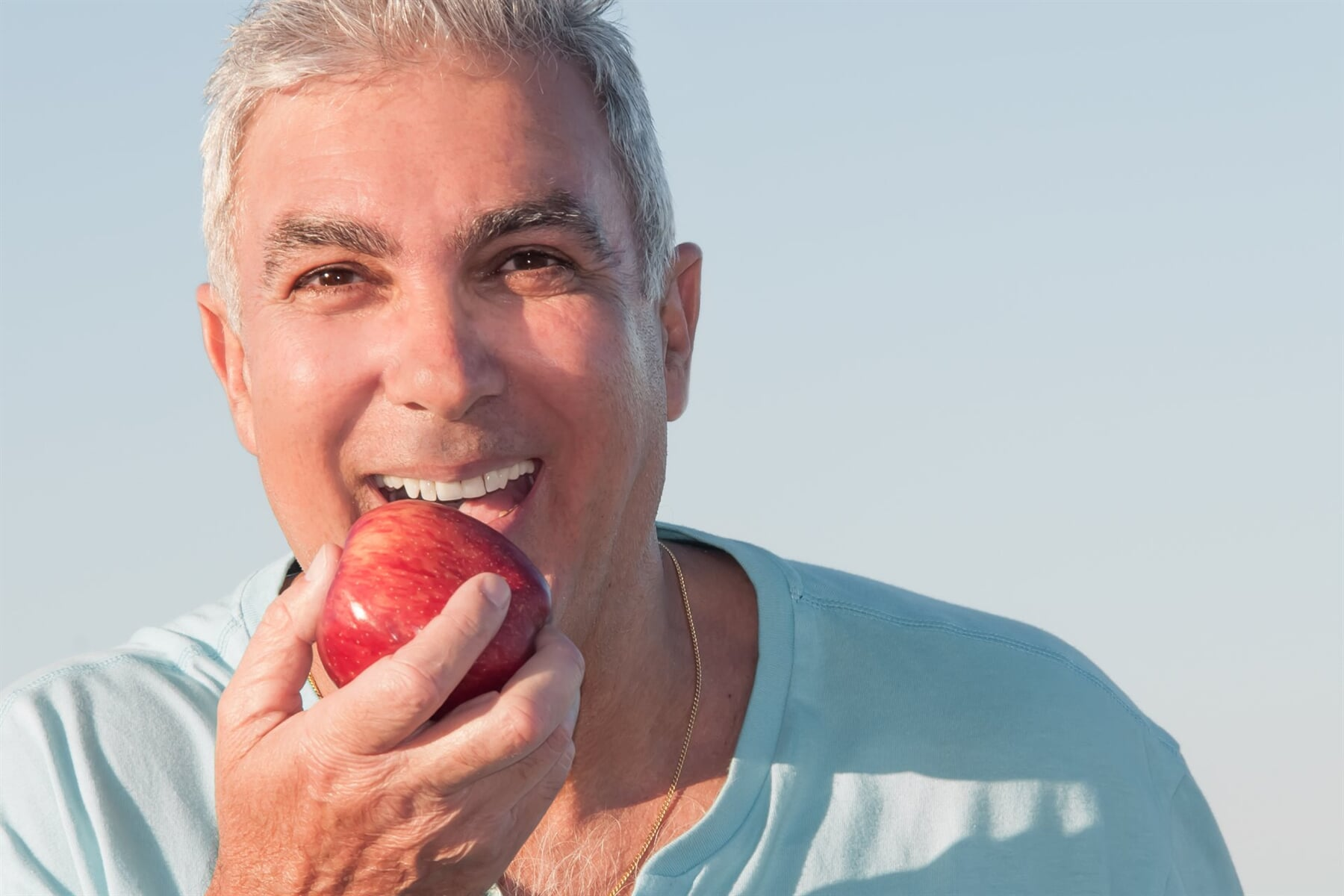 old man eating red apple