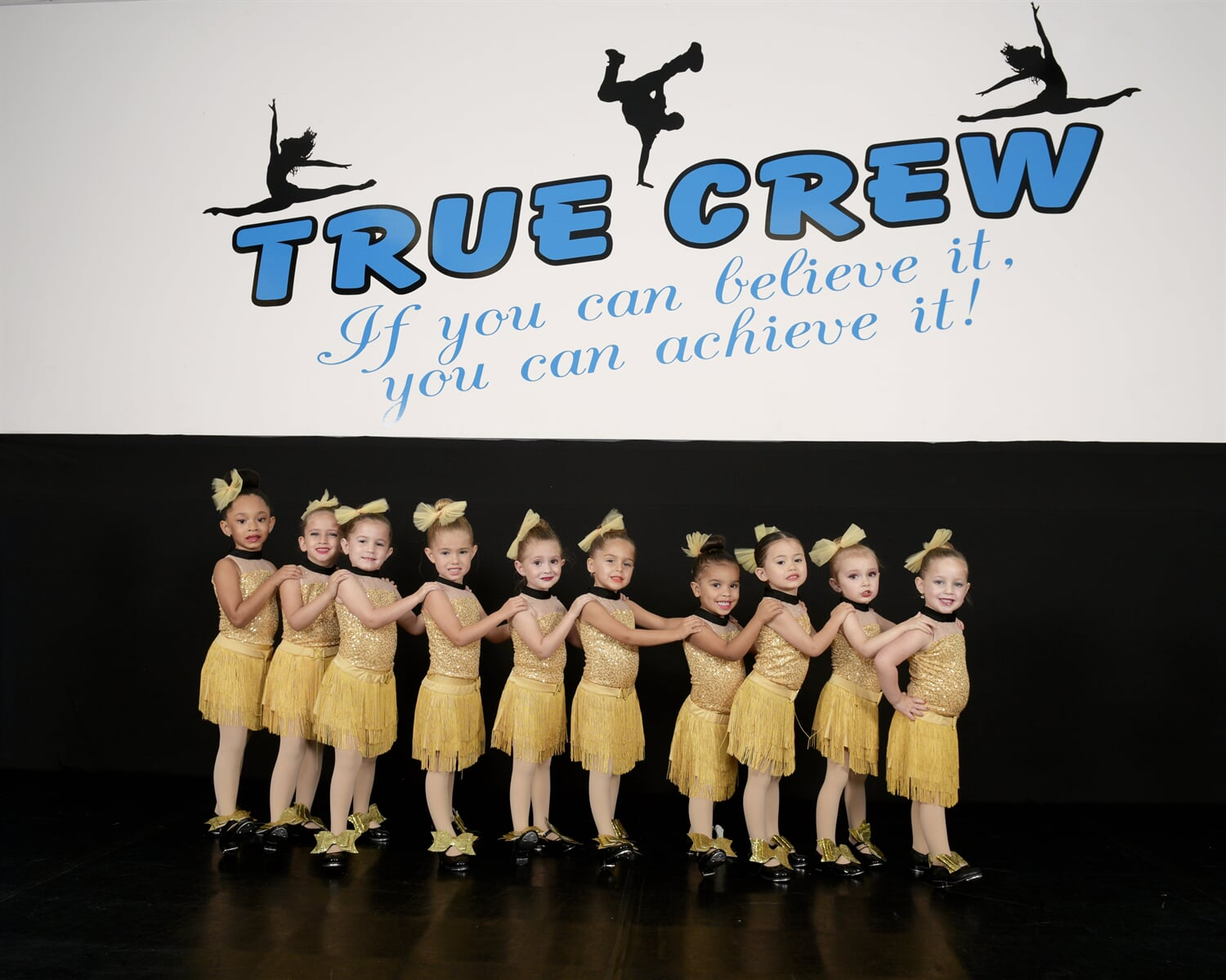 Group of little girls posing in yellow dance costumes
