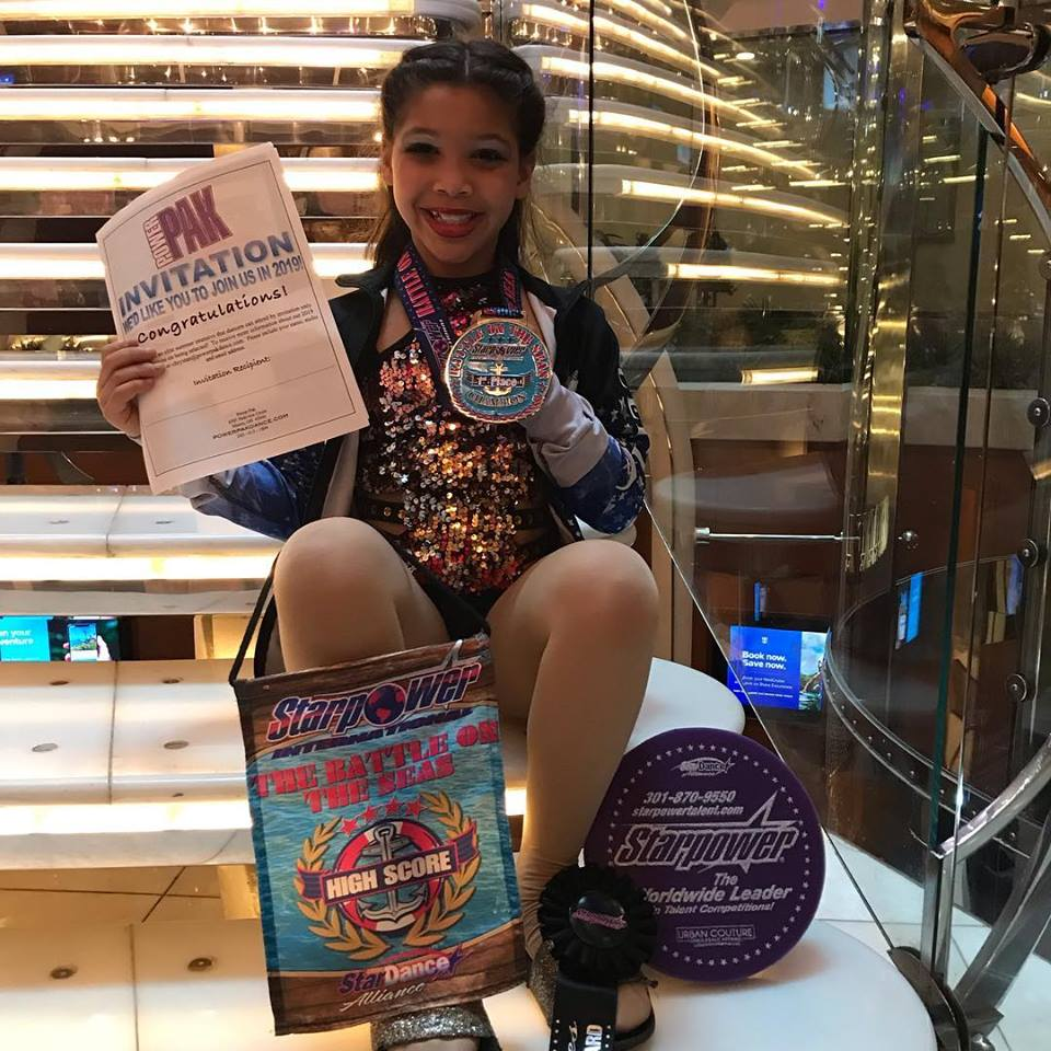 Girl Dancer sitting on stairs displaying medal