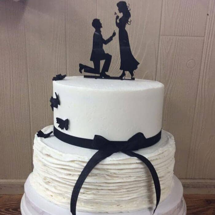 Black and White Wedding Cake with Black Ribbon and Groom Proposing to Bride Cake Topper
