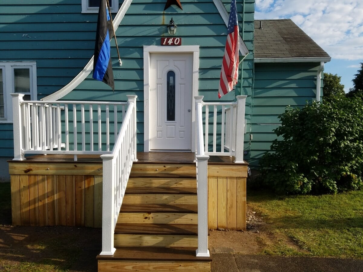Approach to Capecod House featuring new front door and white railings