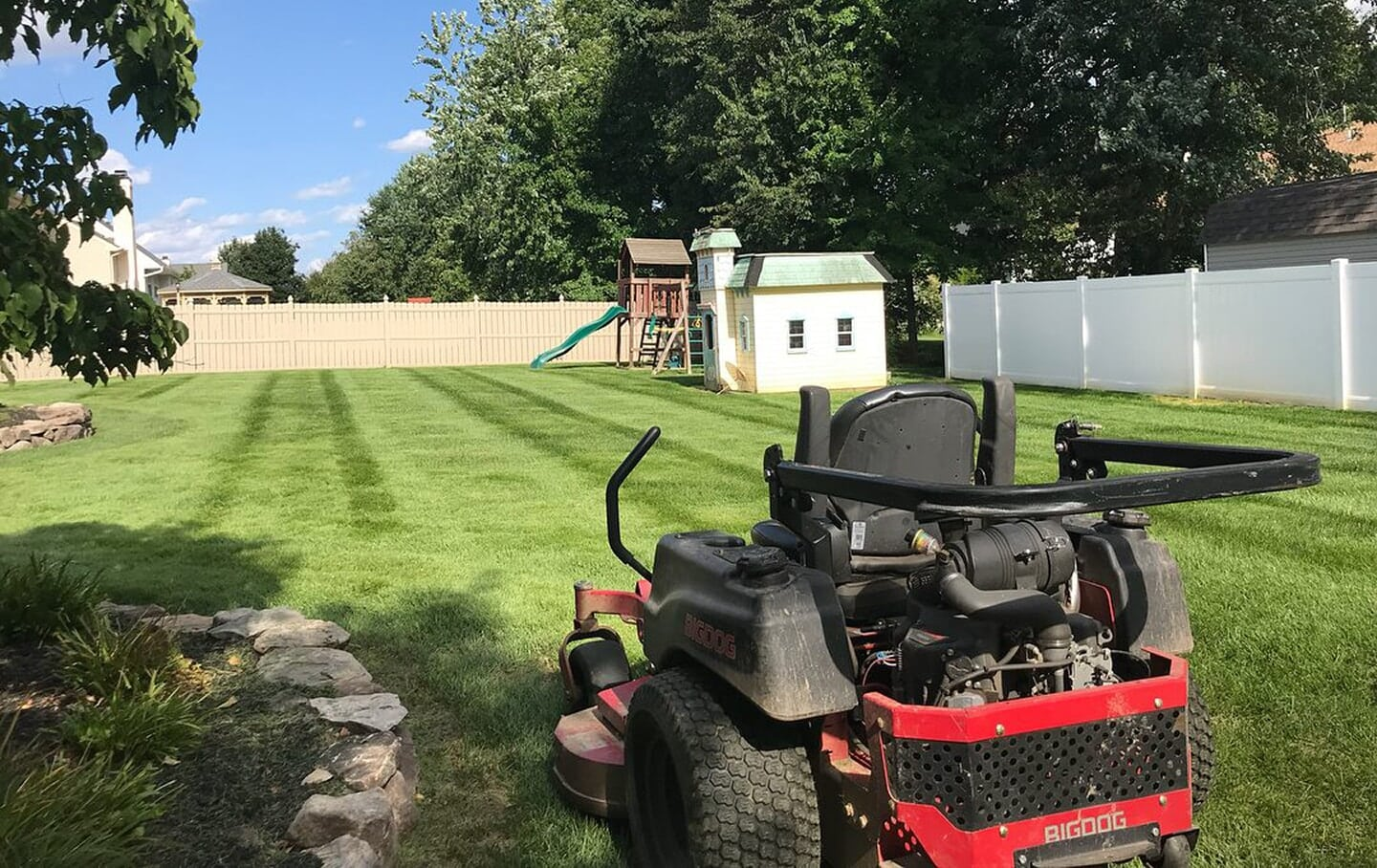 Riding Lawnmower in foreground of back yard