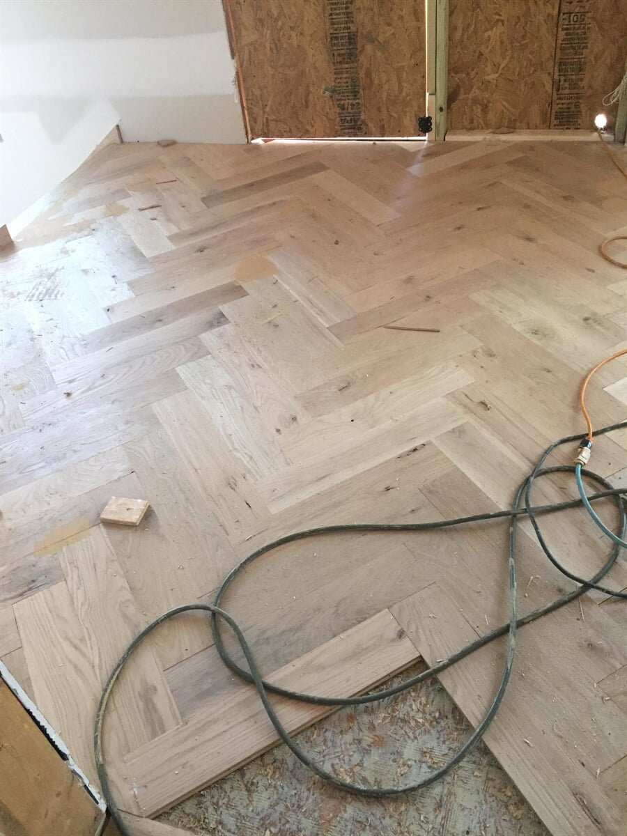 In progress herringbone hardwood install from Carpets Unlimited