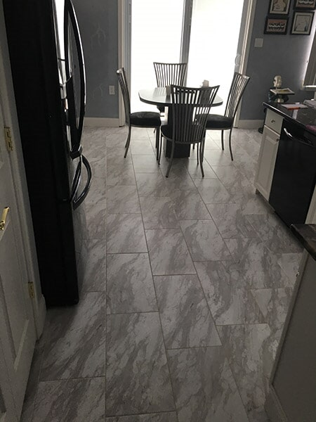 High Performance DuraCeramic Luxury Vinyl Tile floor installed in Howell, NJ in a living room, dining room and kitchen remodel