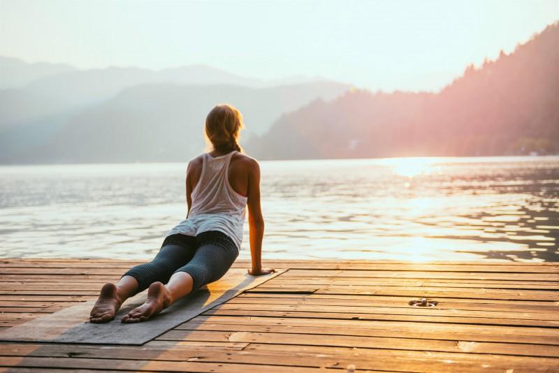 Woman doing yoga on deck overlooking lake