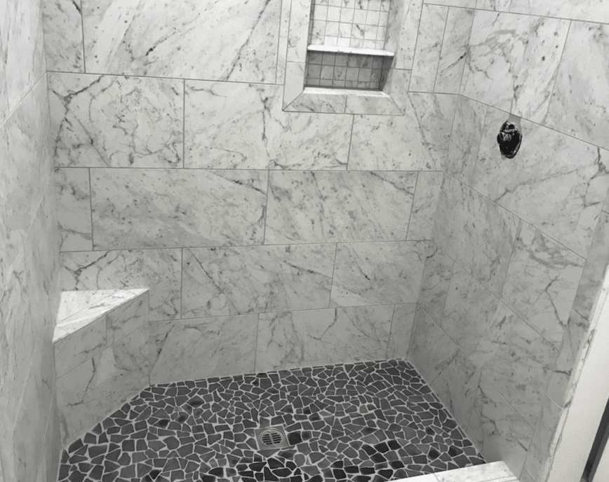 Natural shape tile flooring with marble walls in shower in Valencia, CA