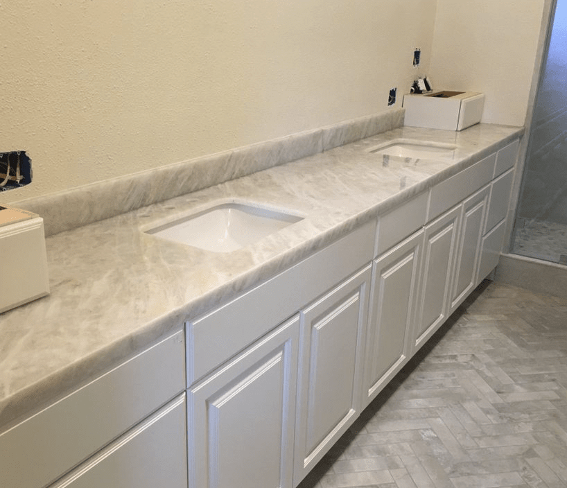 Clean white bathroom vanity with stone countertop in Valencia, CA