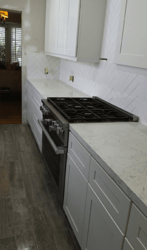 White kitchen design with dark gray flooring in Valencia, CA from Dave Walter Flooring Kitchens and Baths