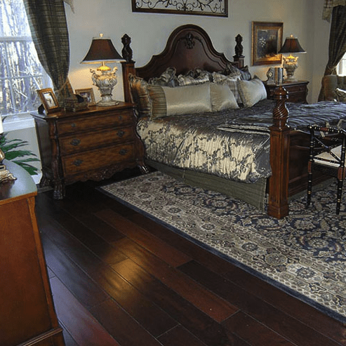 Beautiful dark hardwood flooring in master bedroom in Cary, NC from The Home Center Flooring & Lighting