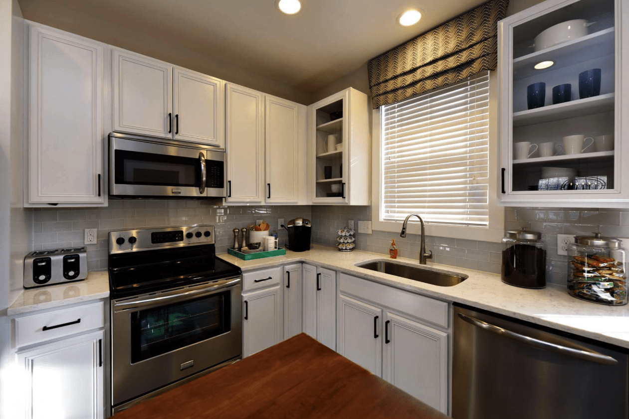 White cabinets with gray subway tile backsplash in Raleigh, NC from The Home Center Flooring & Lighting