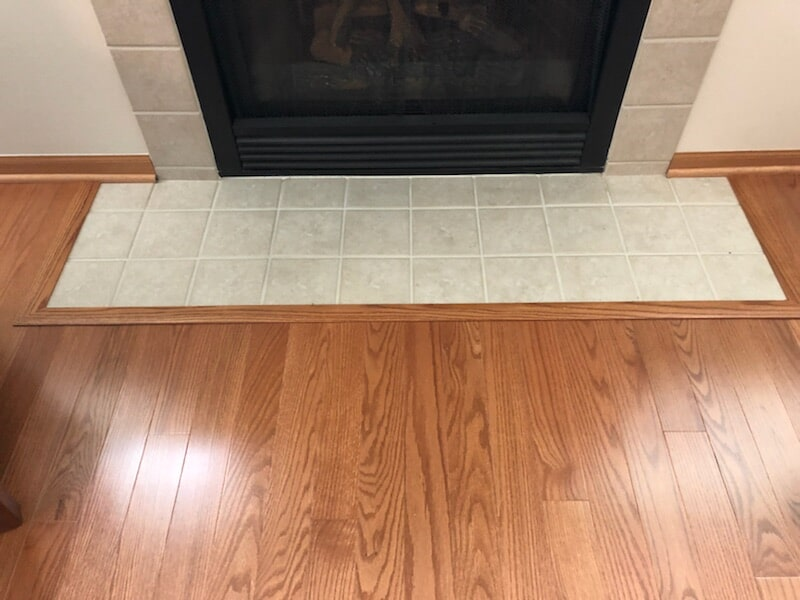 Tile and hardwood fireplace surround in Crest Hill, IL from Marchio Tile & Carpet Inc.