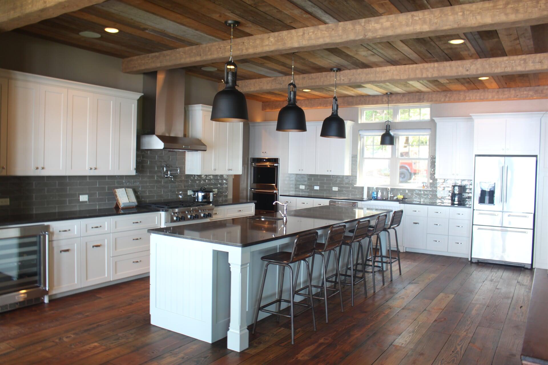 Modern kitchen with dark hardwood floors, white cabinetry, and a gray subway tile backsplash