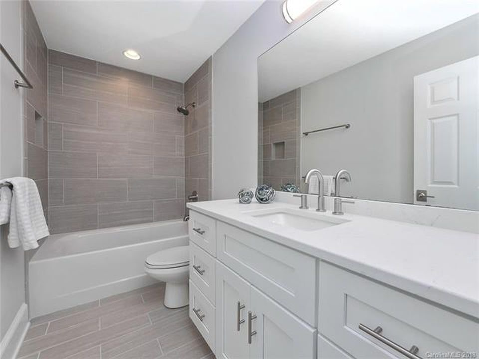 Bright white bathroom renovation with natural tile in Cornelius, NC from LITTLE Wood Flooring & Cabinetry