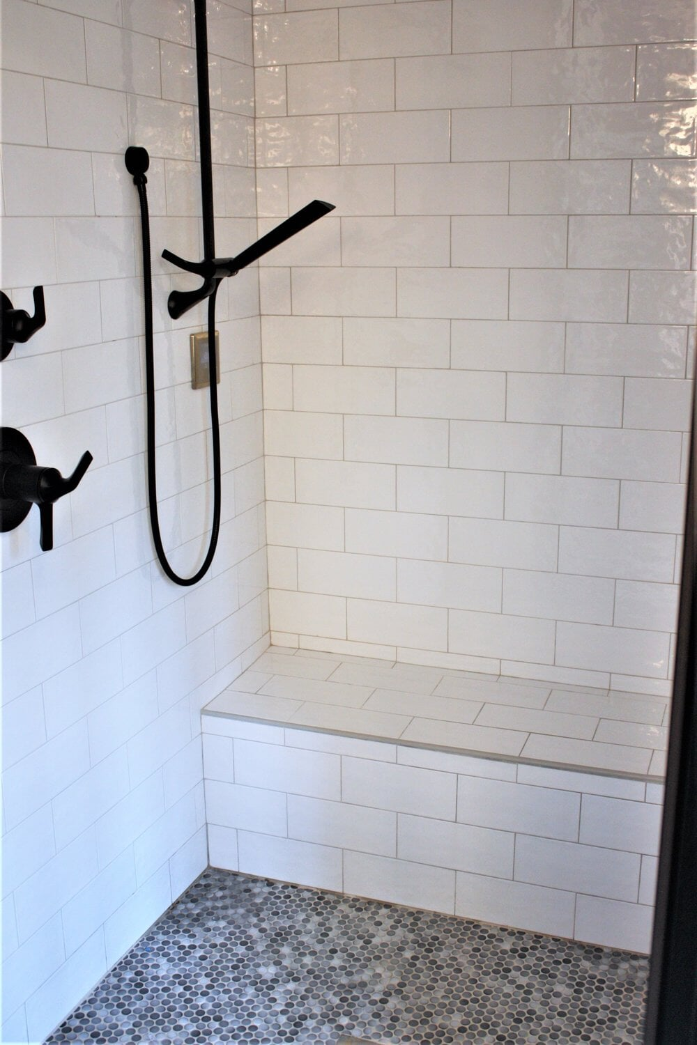 Custom built-in bench in white shower in Cornelius, NC from LITTLE Wood Flooring & Cabinetry
