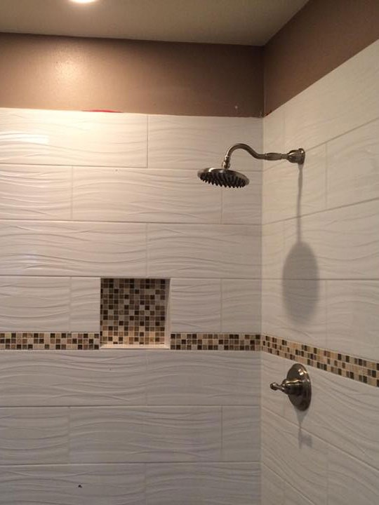 Textured tile shower with accent stripe and recessed shelf in Phoenix, AZ