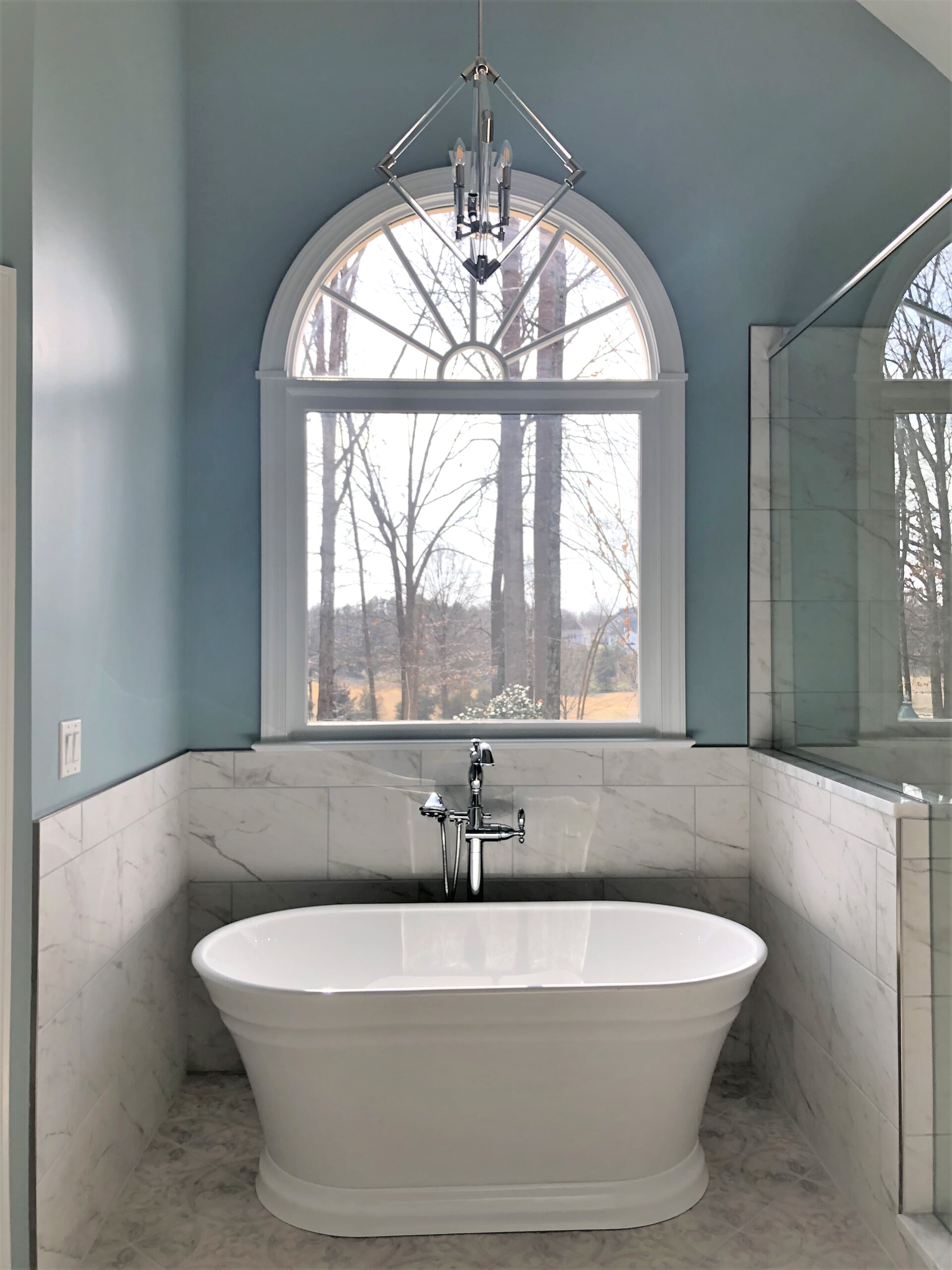 Beautiful soaking tub with white stone walls in Cornelius, NC from LITTLE Wood Flooring & Cabinetry