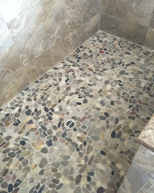Custom shower flooring with round natural stone tiles in Ontario, CA