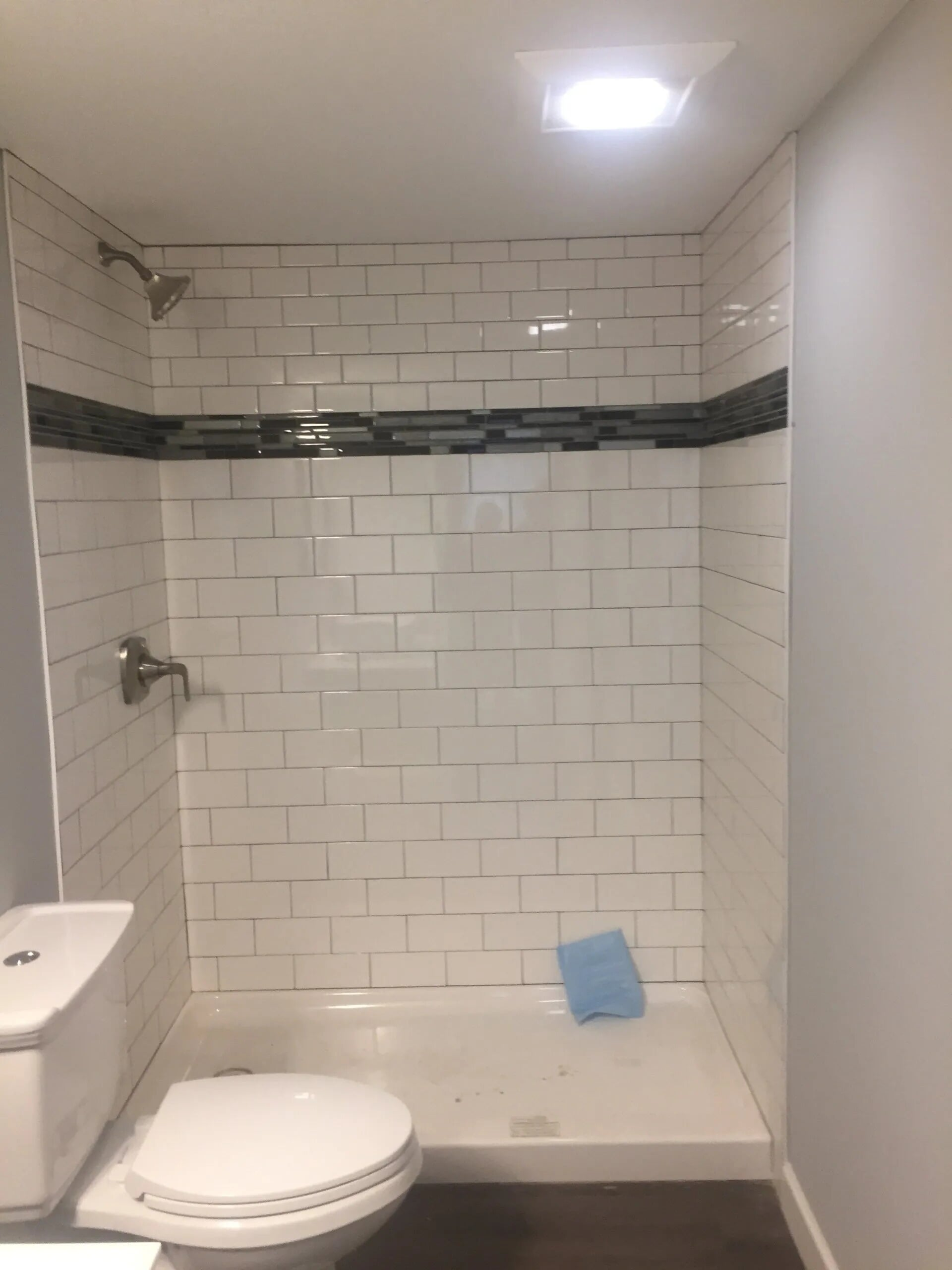 Subway tile shower with accent stripe in Savage, MN from Infinite Floors and More