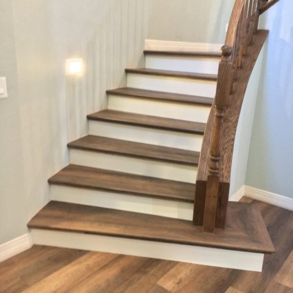 White and wood luxury vinyl stairway in Tempe, AZ from Abel Carpet Tile & Wood