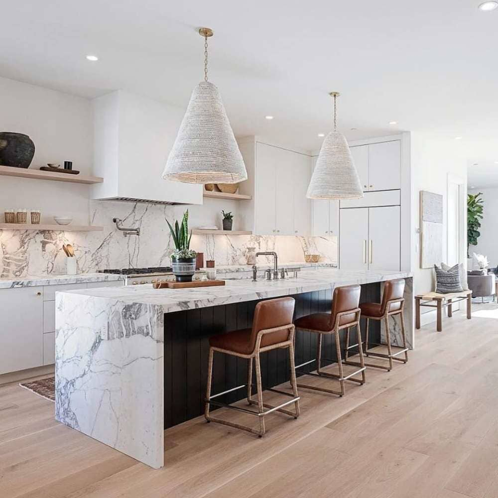 Waterfall marble countertops landing onto classic hardwood flooring available in Stamford, CT