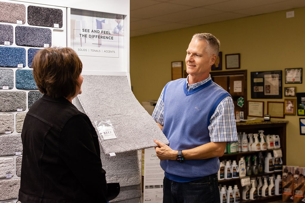 Phil Jr. and Amy of Floors Unlimited admiring a carpet product
