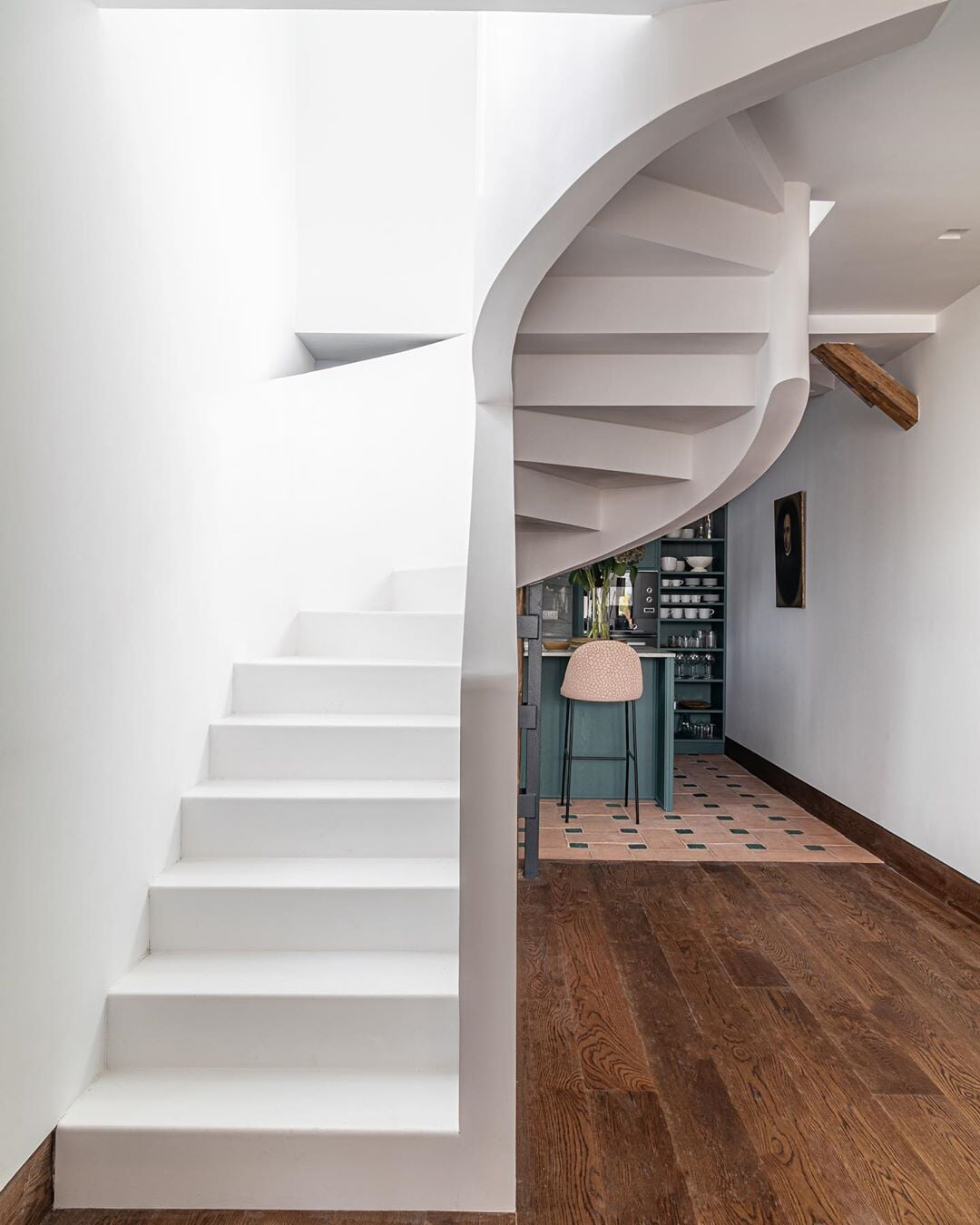 Custom white spiraling staircase in a Bridgeport, CT home with distressed wood flooring