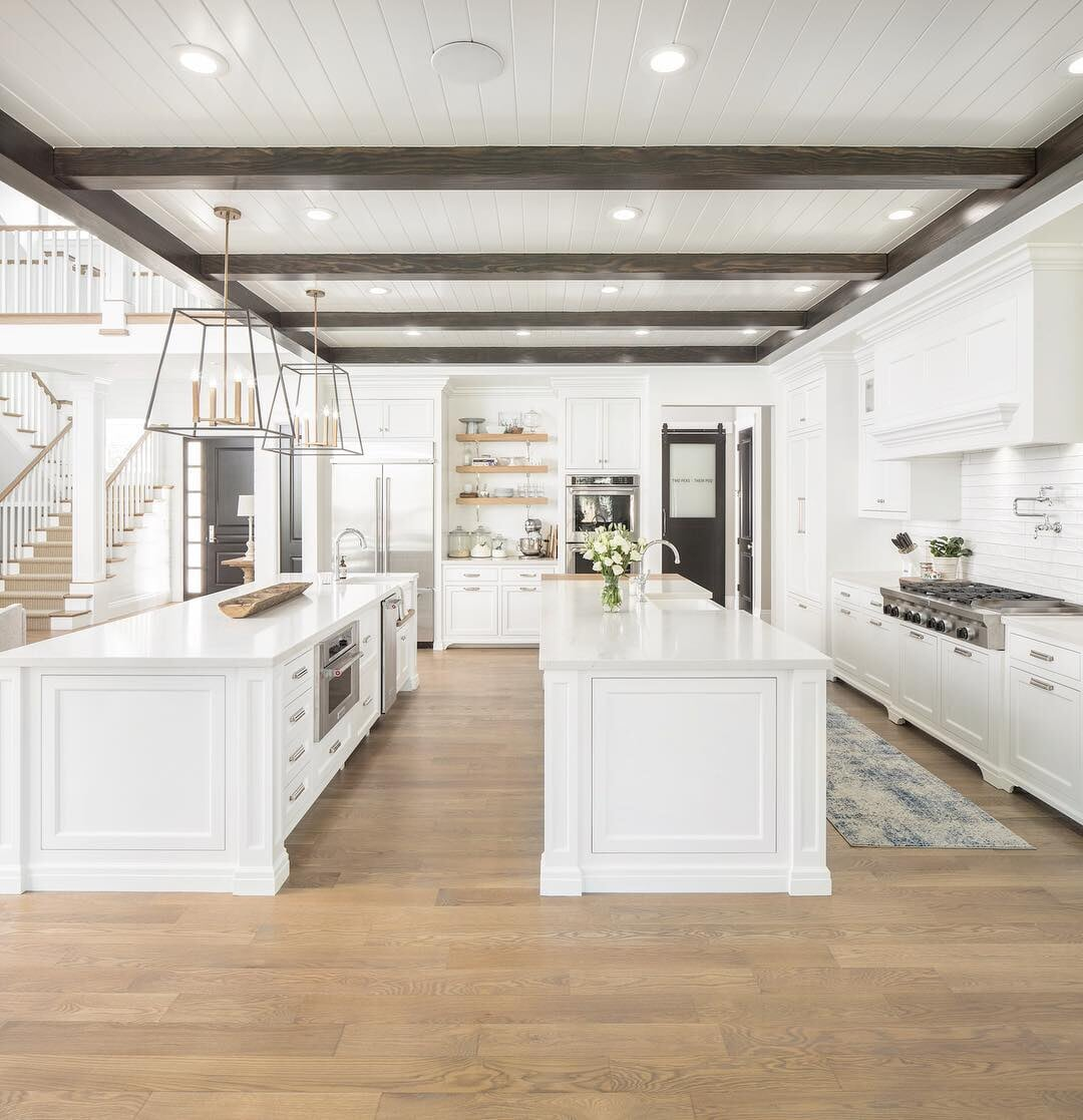Large Stamford, CT kitchen with double islands and light tone engineered hardwood
