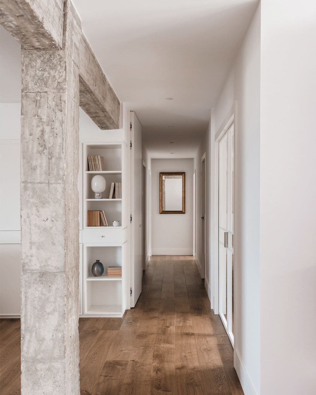 Bridgeport, CT home hallway with exposed concrete beams and wood flooring