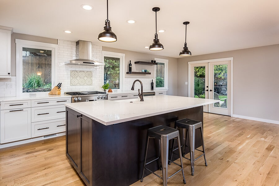 White cabinetry with a dark kitchen island in Seattle, WA from LeBlanc Floors & Interiors