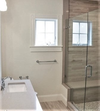 New Seabury Cape Cod - Tiburon Beige Wave Porcelain Wall Tile - Tiburon Beige Floor Shower Bench- Dal Moselle Gris Limestone hexagon shower floor in Yarmouth, MA from Paramount Rug Company